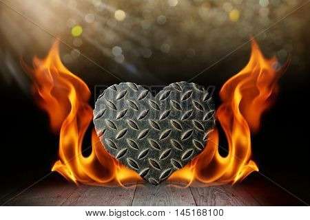 Heart shape steel with blaze fire flame on wooden deck table with bokeh