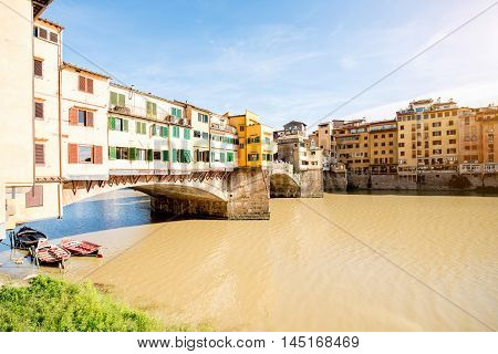 Cityscape view on famous Ponte Vecchio bridge with boats on the river in Florence