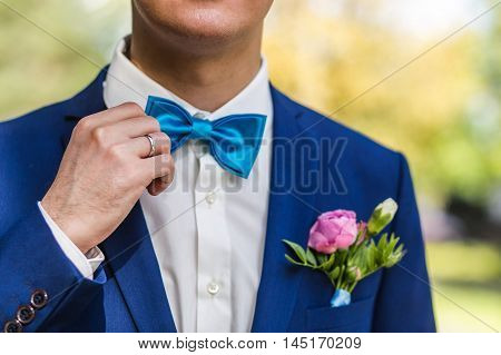 The groom sstraightens a tie . Closeup of the groom in the park on their wedding day.