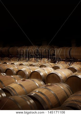 Wine cellar in warm ambiance. Wooden wine barrels at a winery. Balck copy space on top