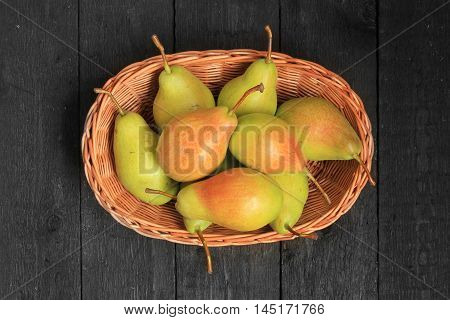 Close up view of ripe pears in a basket on wooden background. View with fresh pears. Top view