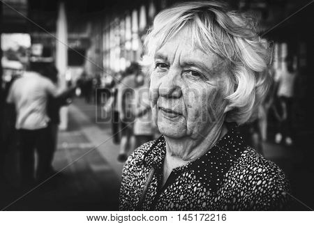 Elderly woman in the city. Black and white photo