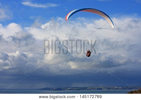 Paraglider flying above Whitsand Bay in Cornwall