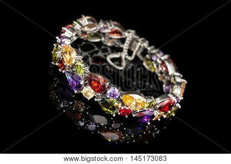 Bracelet with colorful stones isolated on black glass, close-up