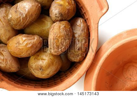 Heap of young baked tasty potatoes in clay pot on white background. Top view