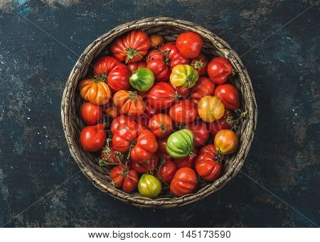 Fresh colorful ripe Fall heirloom tomatoes in basket over grunge dark plywood background, top view, horizontal composition