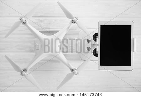 concept drone, tablet and remote control on a white wooden background