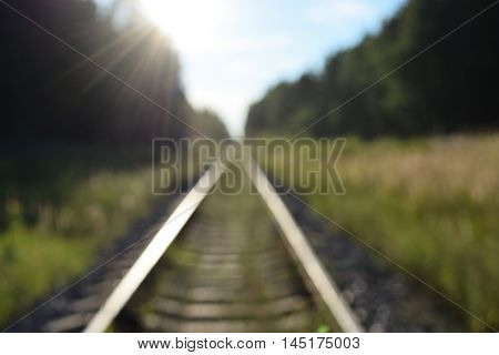 railway tracks stretching into the distance through the forest in bright sun light out of focus background