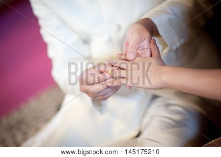 The groom wearing wedding ring for his bride