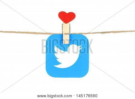 Kiev Ukraine - August 02 2016: Twitter logo printed on paper hangind on a rope with red heart clothespin on a white background