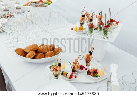 Catering food wedding, white beautiful table. Shrimp, kebabs rolls