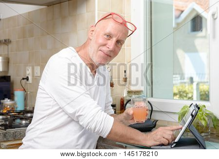 a senior man in kitchen using digital tablet and drink fruit juice