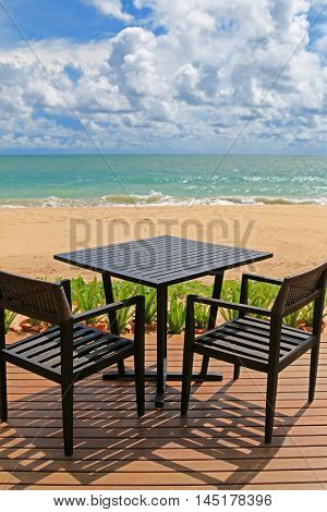 Black table for two on wooden balcony with blurred wave crashing beach and blue sky background in the afternoon, Thailand, Asia