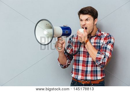 Irritated angry young man in plaid shirt shouting with loudspeaker over grey background