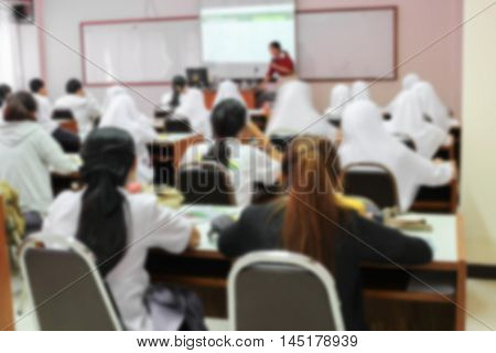 Blur blurred focus of university students sitting in a lecture room with teacher in front of the class with white projector slide screen