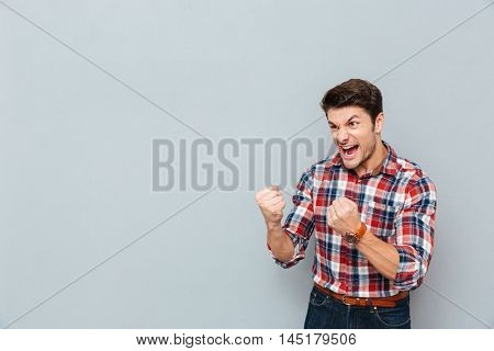 Angry mad young man in plaid shirt showing fists and shouting over grey background