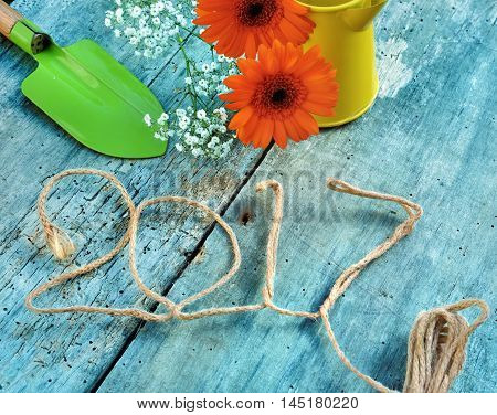 2017 writted with a rope flowers and gardening tools on blue wooden background