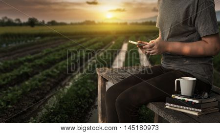 Young woman using her smartphone seriously while sitting outdoor in morning time on weekend with nature view in blurry background. Freelance business working and phone addiction concept