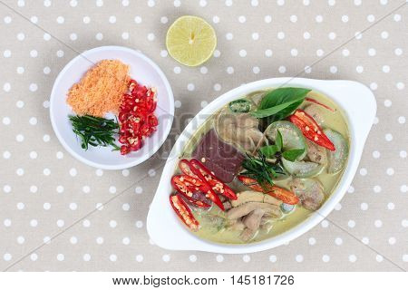 Green chicken curry in coconut milk served with side dish as minced dried shrimp,sliced red chili,sliced kaffir lime leaves and green lemon on gray.