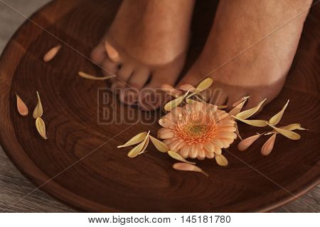Female feet in spa wooden bowl with flowers, closeup
