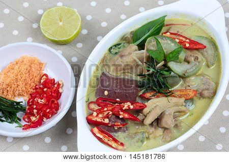 Green chicken curry in coconut milk served with side dish as minced dried shrimp,sliced red chili,sliced kaffir lime leaves and green lemon on gray. Close up.