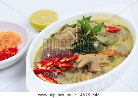 Green chicken curry in coconut milk served with side dish as minced dried shrimp,sliced red chili,sliced kaffir lime leaves and green lemon on white background. Selective focus.