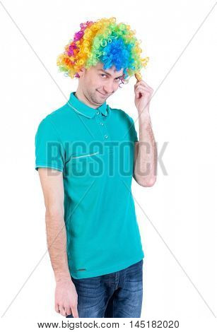 Portrait of a man in a clown wig. guy silly smiles. clown in colored wig looks shyly into the frame.