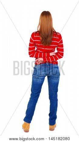 back view of standing young beautiful woman. blonde in a red striped sweater standing with hands clasped behind his back.