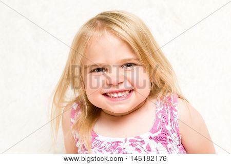 Closeup Portrait of Beautiful Toddler Girl Grinning Cheekily on Neutral Background