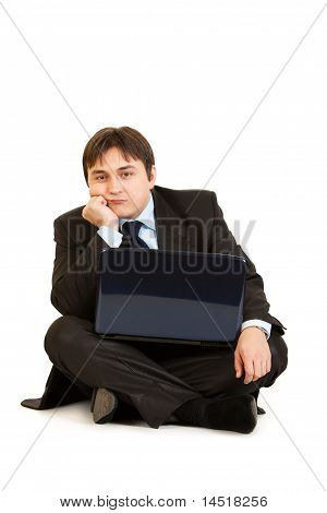 Bored businessman sitting on floor with laptop isolated on white