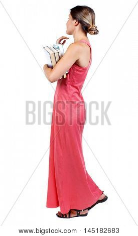 Girl comes with stack of books. side view. slender woman in a long red dress looking to the side while holding a book in his hands.