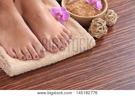Female feet with brown pedicure and flowers on towel