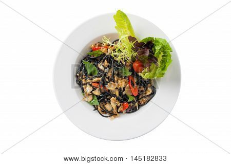Top view of Italian and Thai fusion food style spicy black pasta with clams garnished with red chili and vegetables in ceramic dish isolated on white bckground