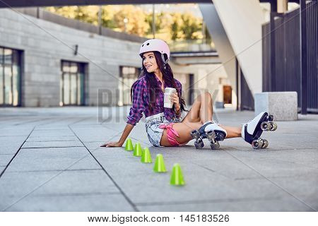 Happy young girl enjoying roller skating with coffee, rollerblading on retro skates sport in urban park. Young woman have a rest after rollerblading and drinking coffee