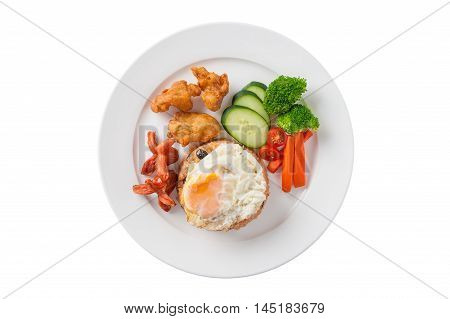 Top view of Thai style cuisine fried rice with raisin deep fried chicken sausage and fried egg garnished with vegetables in ceramic dish isolated on white background