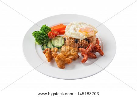 Front view of Thai style cuisine fried rice with raisin deep fried chicken sausage and fried egg garnished with vegetables in ceramic dish isolated on white background