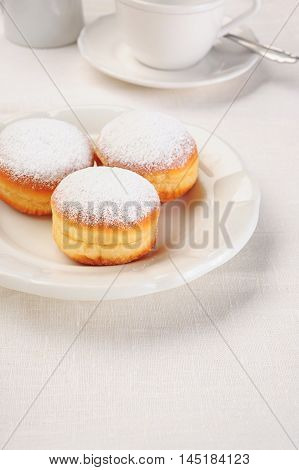 three doughnuts on white plate and coffee cup