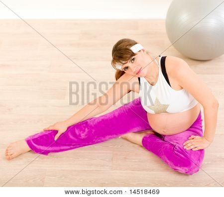 Smiling pretty pregnant woman doing stretching exercises
