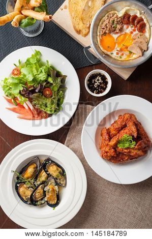 Top view of modern cuisine set including spring rolls pan fried egg Korean style deep fried chicken baked mussels and Japanese crab stick salad on wood table in restaurant