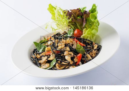 Italian and Thai fusion food style spicy black pasta with clams garnished with red chili and vegetables in ceramic dish