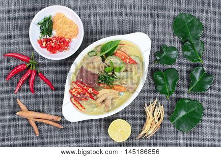 Green chicken curry in coconut milk served with side dish as minced dried shrimp,sliced red chili,sliced kaffir lime leaves and green lemon.