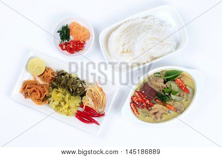 Rice noodle and green chicken curry in coconut milk with side dish as red pepper,pickle lettuce,minced dried shrimp,sliced correspondents,sliced red chili - kaffir lime leaves,radish and green lemon.