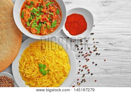 Tasty dinner with chicken curry and rice in plates on wooden background