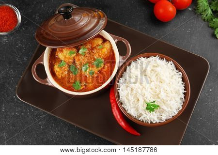 Tasty dinner with chicken curry in saucepan and rice in bowl
