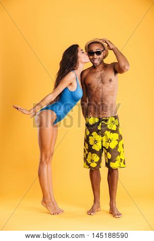 Pretty girl in swimsuit kissing her african boyfriend isolated on orange background