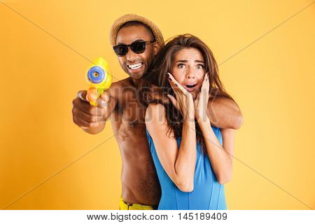 Young happy multiracial couple having fun playing with water guns isolated on the orange background
