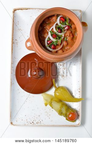 beans baked in a ceramic pot decorated with onion rings and pomegranate seeds