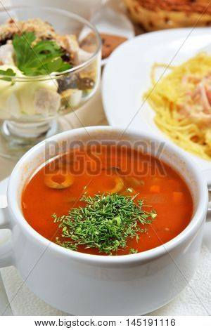 tomato soup with greens and olives. beautiful image
