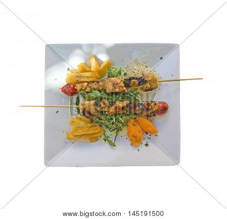 Chicken skewers with grilled tomatoes on rucola salad with fries and pumpkin mousse on a plate aerial view isolated on white.