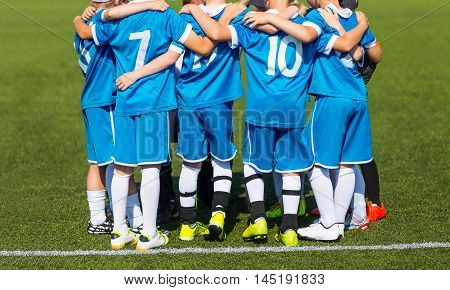 Kids with soccer coach gathering before match. Youth soccer football team. Group photo. Soccer players standing together united. Soccer team huddle. Teamwork team spirit and teammate example.